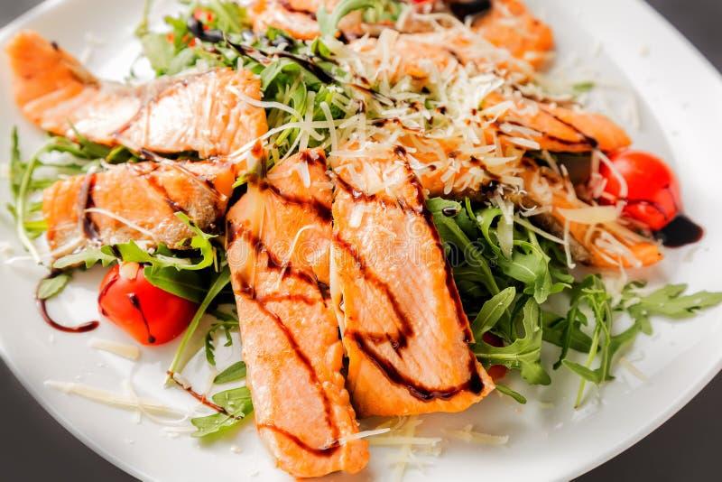 三文鱼片断、西红柿、莴苣、乳酪和调味汁新鲜的沙拉在白色板材关闭 免版税图库摄影