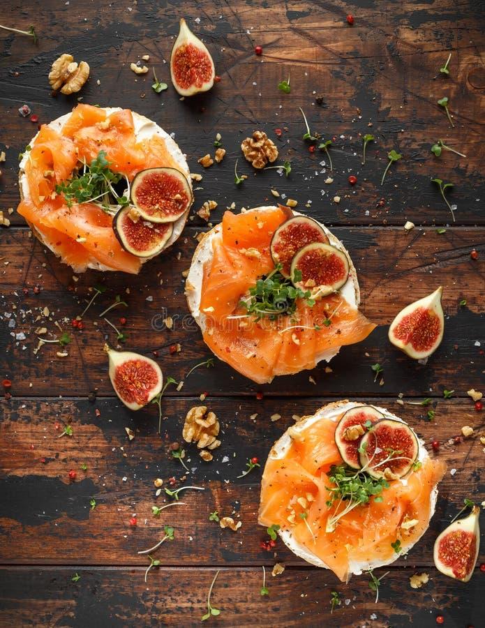 三文鱼百吉卷三明治用无花果、水芹沙拉、核桃,乳脂干酪和五谷在土气木背景 健康 免版税库存图片
