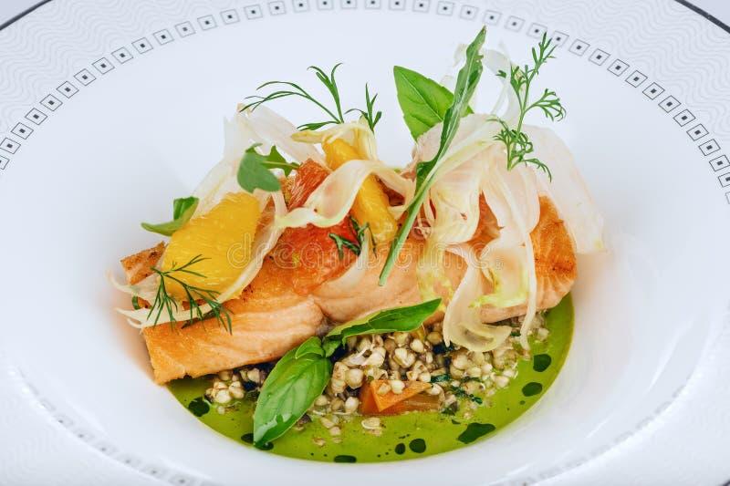 三文鱼红色鱼片烹调了与在白色板材隔绝的新鲜的蔬菜沙拉叶子特写镜头 免版税库存照片
