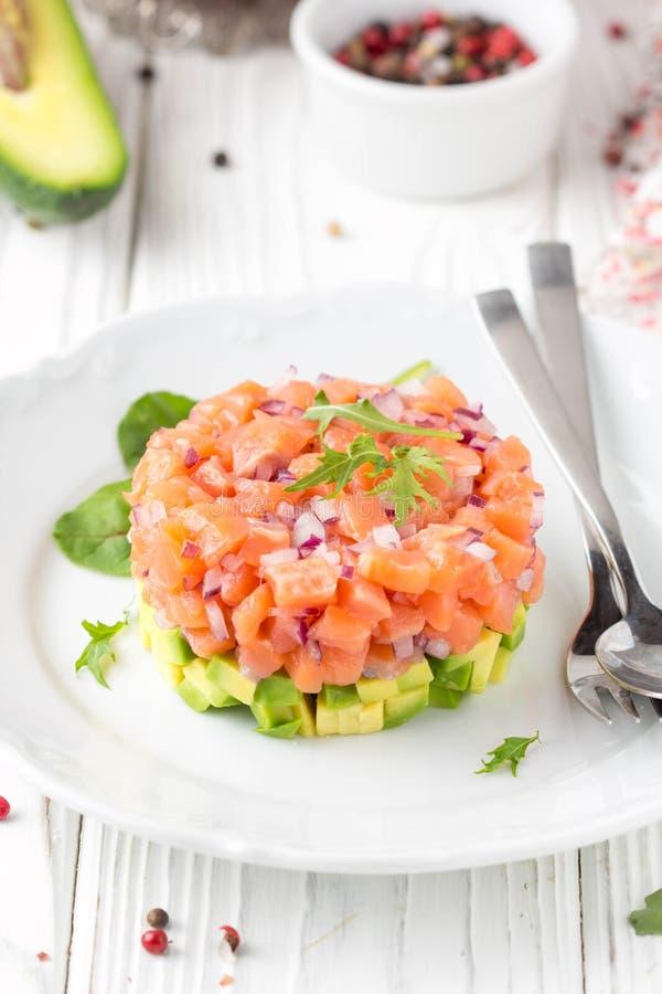 三文鱼鞑靼用红洋葱,鲕梨,芝麻菜,面包多士美丽的快餐,饮食食物,开胃菜为圣诞节假日 ? 图库摄影