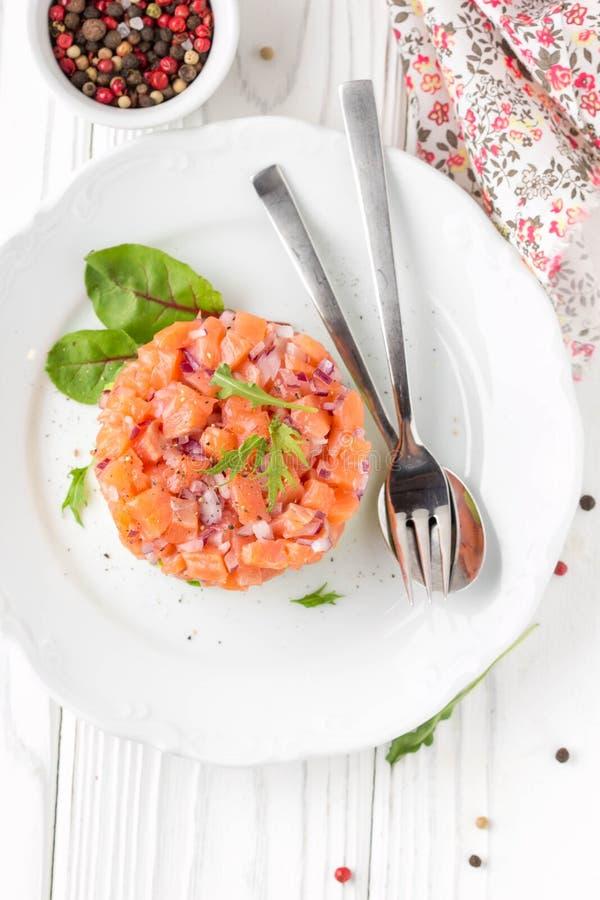 三文鱼鞑靼用红洋葱,鲕梨,芝麻菜,面包多士美丽的快餐,饮食食物,开胃菜为圣诞节假日 ? 库存照片
