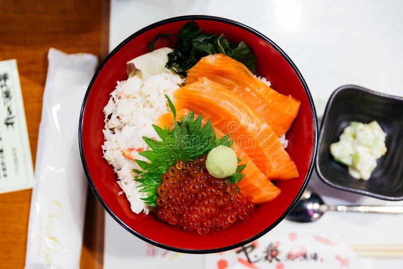 三文鱼饭碗服务与ikura三文鱼獐鹿、螃蟹、海草和山葵在餐馆在札幌在北海道,日本 免版税库存图片