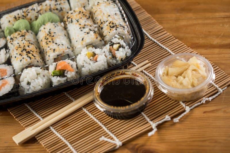 三文鱼,鲕梨和芒果里里外外加利福尼亚寿司用酱油,烂醉如泥的姜、酱油和木筷子在塑料 免版税库存照片