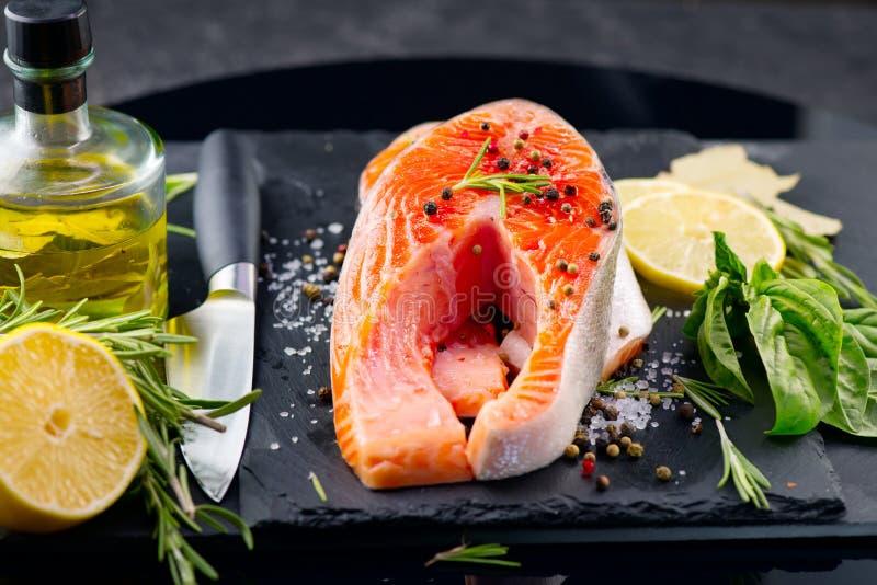 三文鱼 未加工的鳟鱼鱼排用草本和柠檬在黑板岩背景 烹调,海鲜 图库摄影