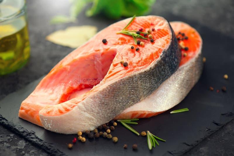 三文鱼 未加工的鳟鱼鱼排用草本和柠檬在黑板岩背景 烹调 免版税库存照片