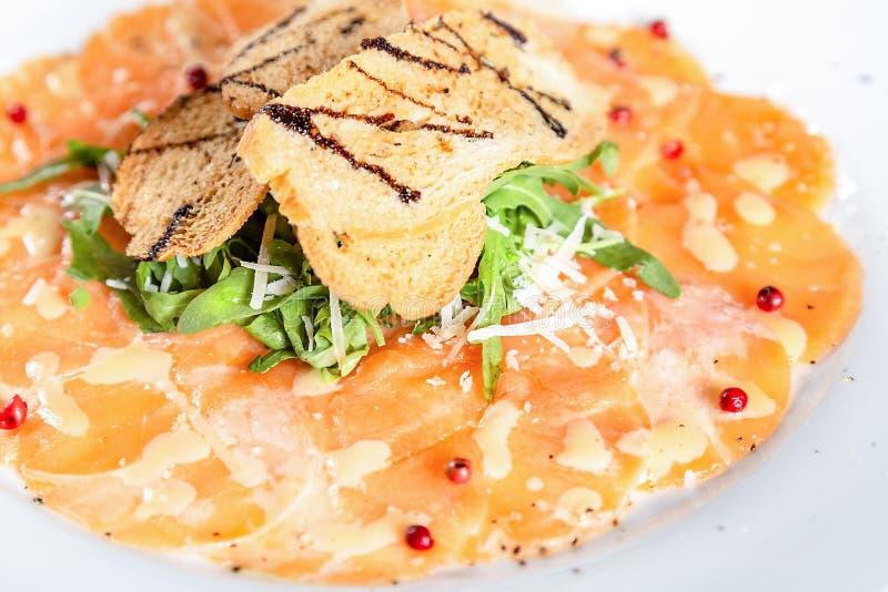 三文鱼Carpaccio用火箭沙拉和油煎方型小面包片 图库摄影