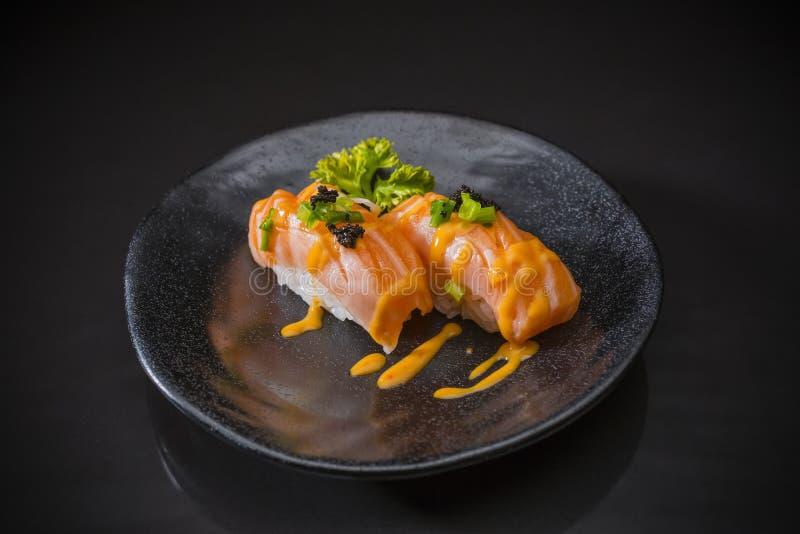 三文鱼Nigiri,寿司三文鱼烧了并且冠上了用虾鸡蛋 免版税图库摄影