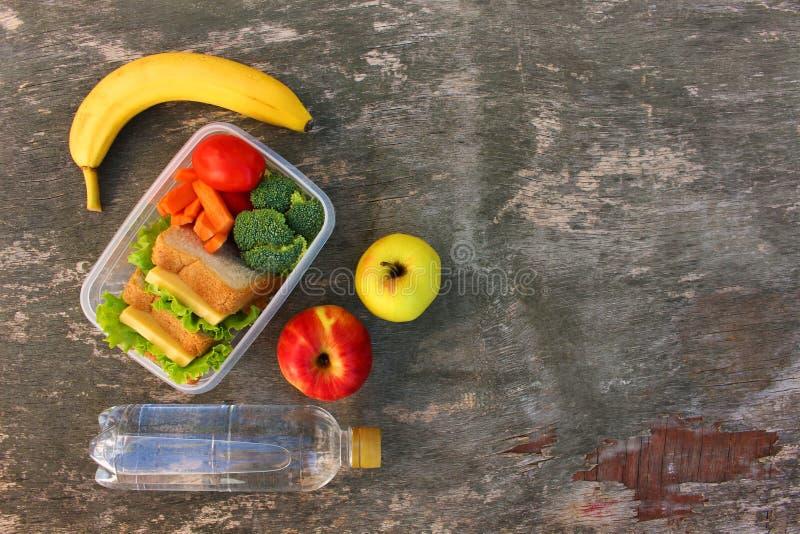 三明治、水果和蔬菜在食物箱子,水 免版税库存图片