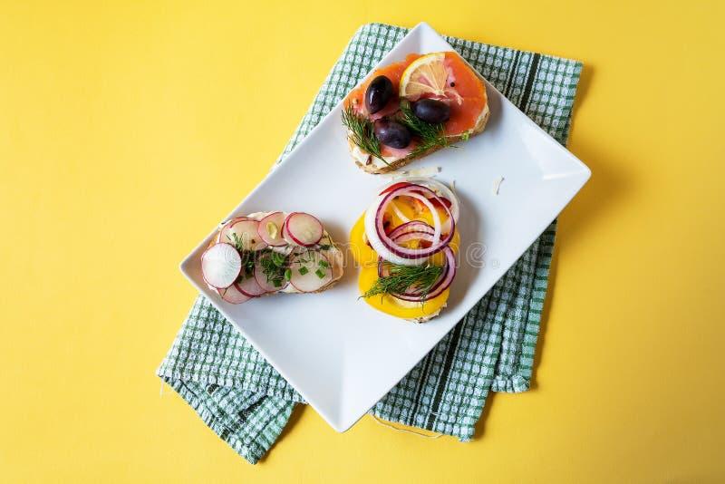 三明治准备与奶油奶酪、菜和三文鱼,在一块板材,在餐巾 午餐或早餐拷贝的健康食品 库存照片