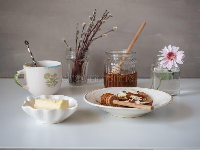 三明治可口午餐用黄油和蜂蜜 在一个玻璃瓶子倒了蜂蜜 在花瓶的小花束 整个构成 免版税库存照片