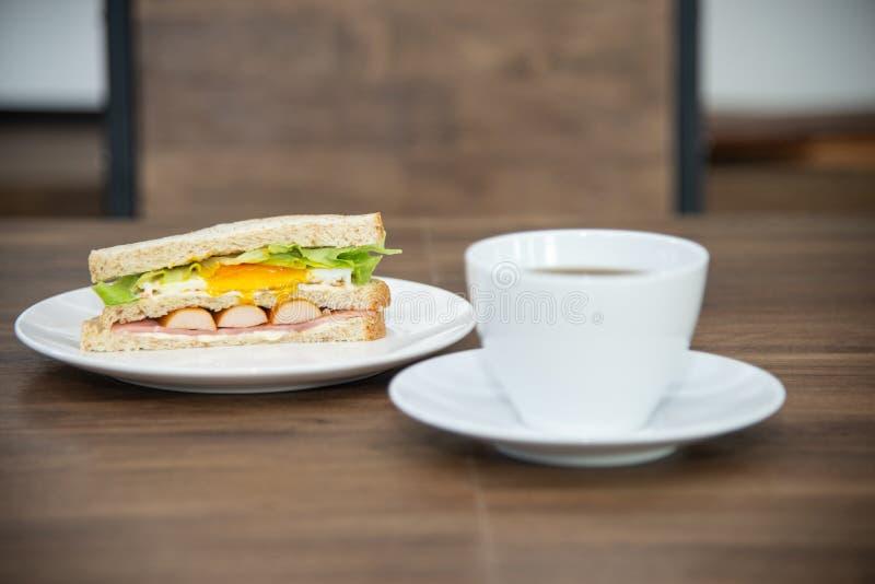 三明治和咖啡在白色板材和木桌,三明治的由面包,香肠,荷包蛋被做,并且vetgetable是 库存图片