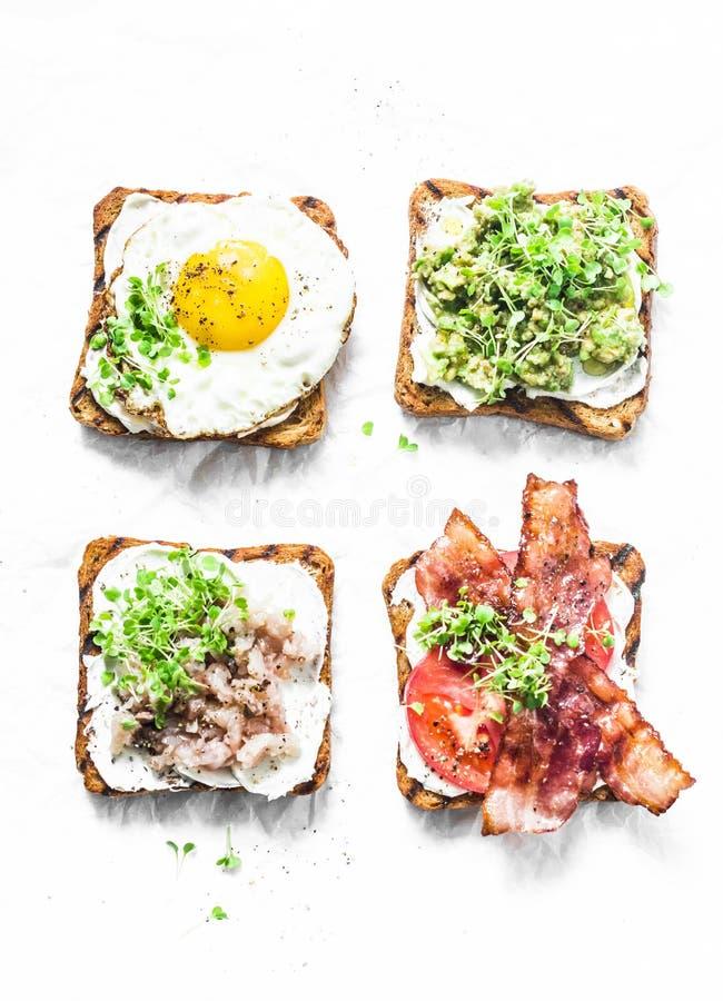 三明治品种早餐,快餐,开胃菜-鲕梨纯汁浓汤,荷包蛋,蕃茄,烟肉,奶油奶酪,熏制的鲭鱼 库存图片