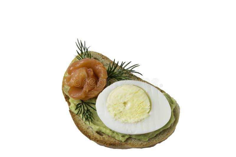 三明治用三文鱼鸡蛋和鲕梨在白色背景 免版税库存图片