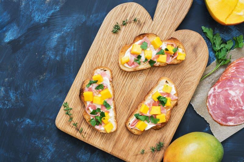 三明治用乳脂干酪、火腿和芒果在一个木板,蓝色背景 看法从上面,平的位置 免版税库存图片