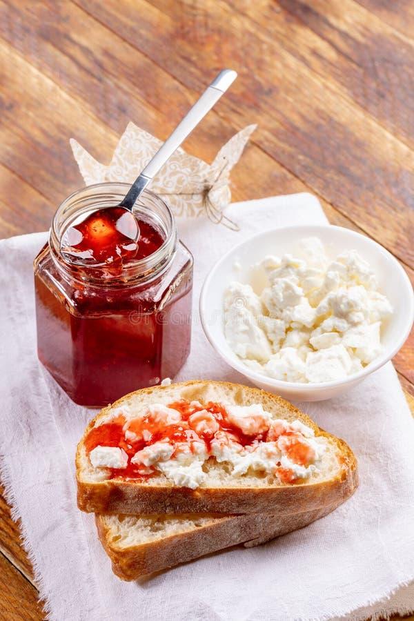 三明治用凝乳和草莓酱,瓶子草莓酱和碗用在白色餐巾的凝乳在木桌上 免版税图库摄影