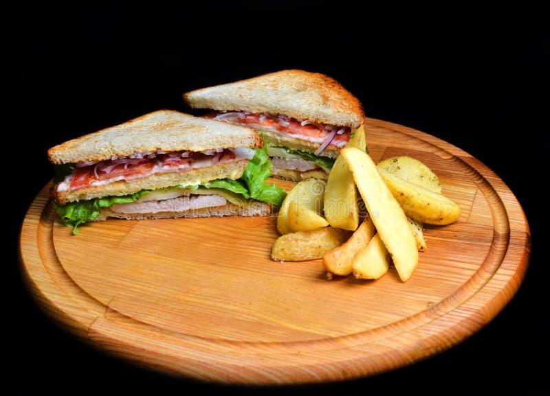 三明治用在白色背景隔绝的一个木板的被烘烤的土豆 Restaurated食物 快餐 库存照片