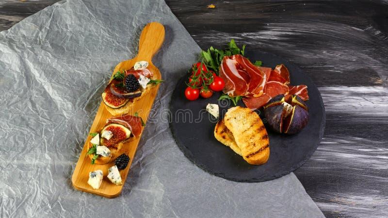 三明治用无花果、青纹干酪和熏火腿 开胃小菜食家bruschetta快餐 平的位置,拷贝空间 免版税库存照片