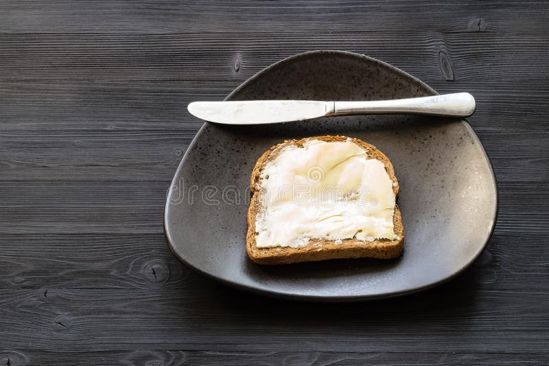 三明治用涂奶油的黄油和刀子在黑色 免版税库存图片