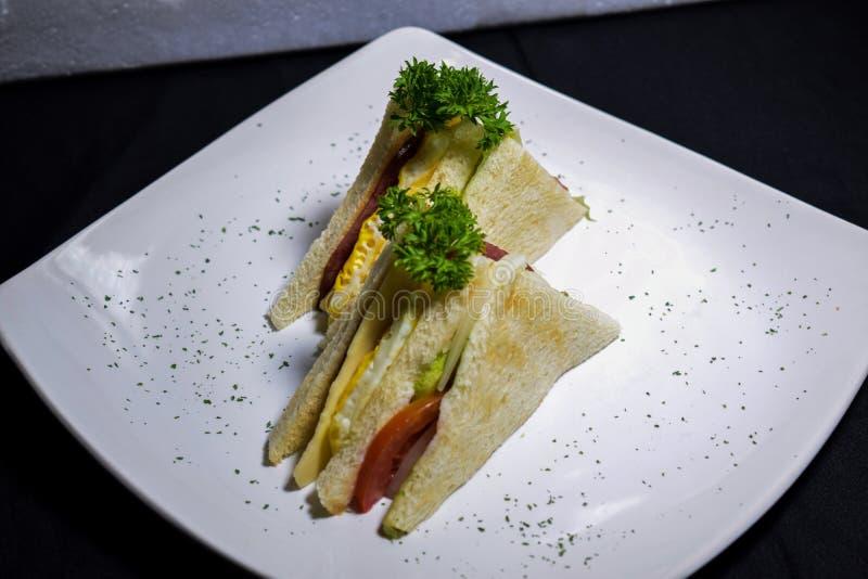 三明治用火腿、乳酪、蕃茄、莴苣和敬酒的面包 在黑背景的看法葡萄酒上 免版税图库摄影