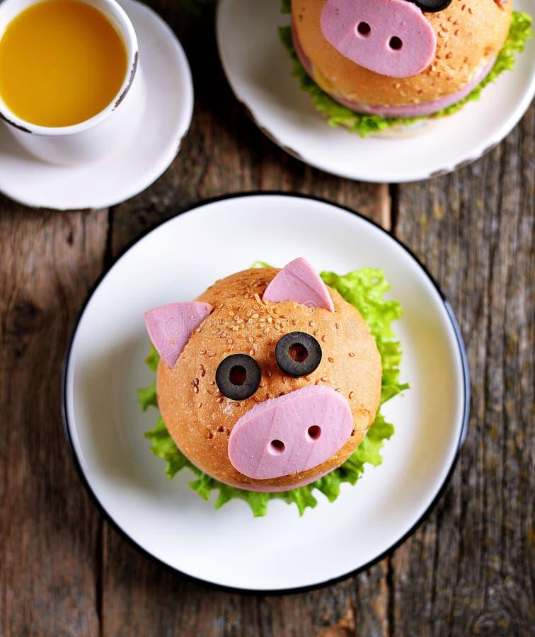 三明治用火腿、乳酪和莴苣以逗人喜爱的猪- 2019年的标志的形式 儿童的早餐圣诞节背景 名列前茅vi 免版税库存图片