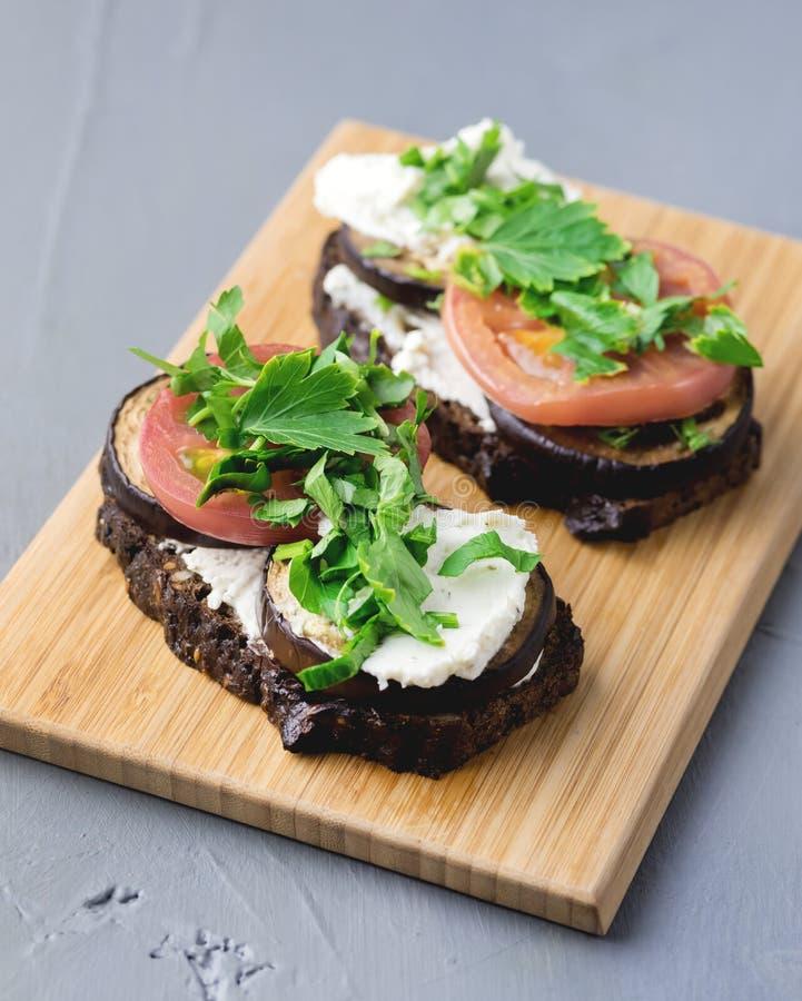 三明治用烤菜夏南瓜Eggplan蕃茄有酸奶干酪木背景Bruschetta 免版税库存照片
