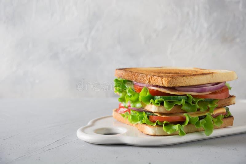 三明治用白色多士面包,烟肉,蕃茄,葱,沙拉,在光的乳酪 文本的空间 图库摄影