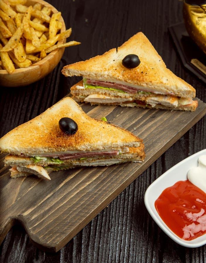 三明治用蒜味咸腊肠、烟肉和薯条 免版税库存照片