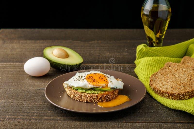 三明治用鲕梨和一个煎蛋在一块棕色板材在土气木头和桌面包在绿色洗碗布 免版税库存图片
