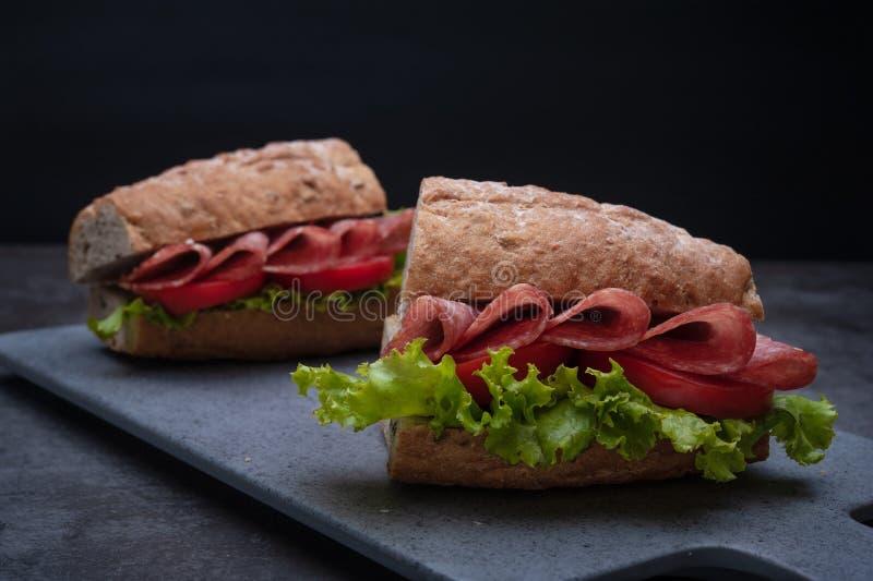 三明治蒜味咸腊肠tamato莴苣背景 免版税图库摄影