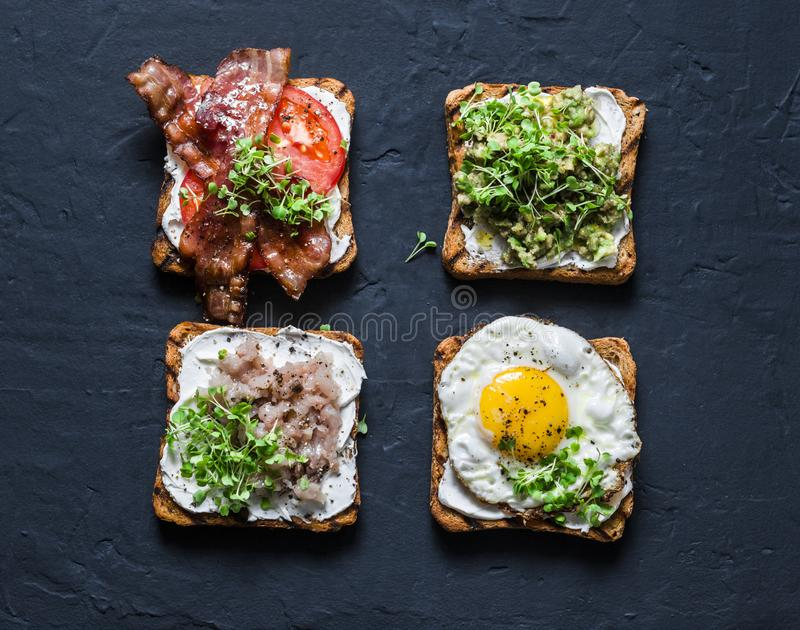 三明治选择早餐,快餐,开胃菜-鲕梨纯汁浓汤,荷包蛋,蕃茄,烟肉,奶油奶酪,熏制的鲭鱼g 免版税库存照片