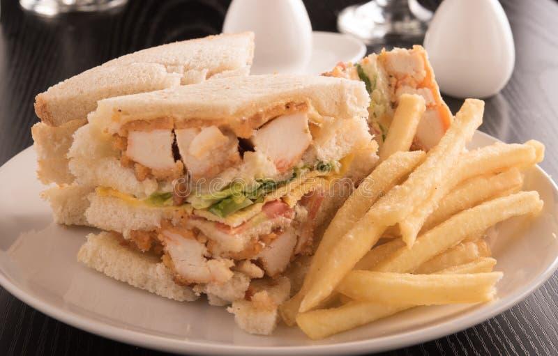 三明治和炸薯条在一块白色板材 免版税图库摄影