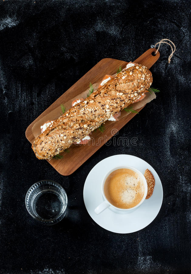 三明治(熏制鲑鱼、酸奶干酪,莳萝),咖啡和水 免版税库存图片