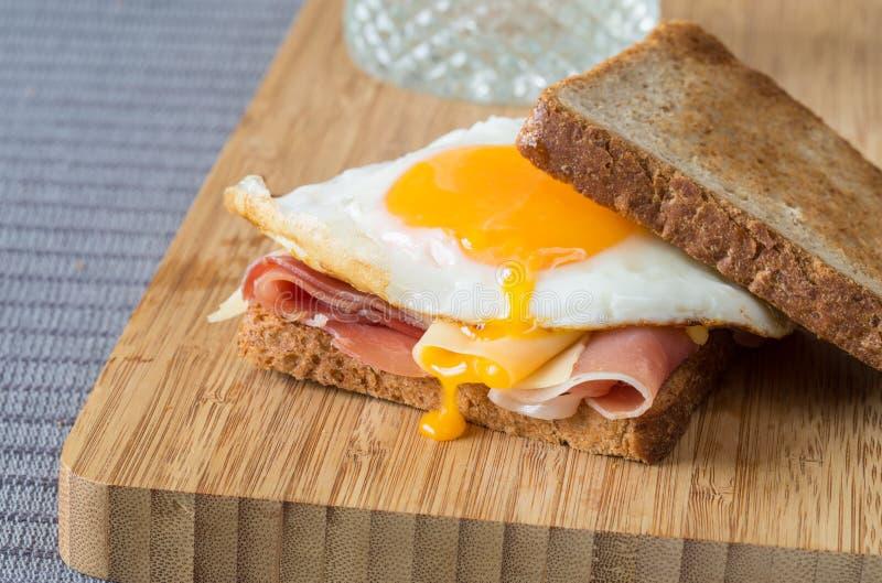三明治用一个煎蛋、乳酪和火腿 免版税库存照片