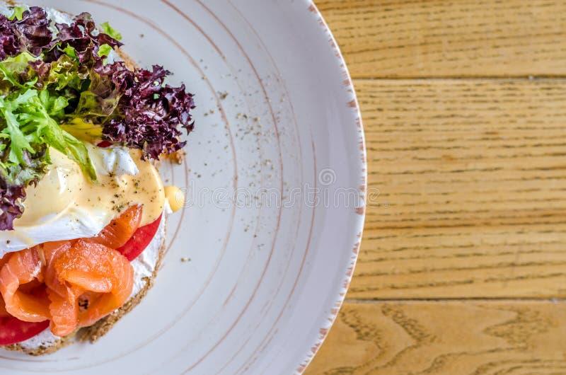 三明治用红色鱼乳酪和草本在一块板材,在一张木桌上,看法从上面 图库摄影
