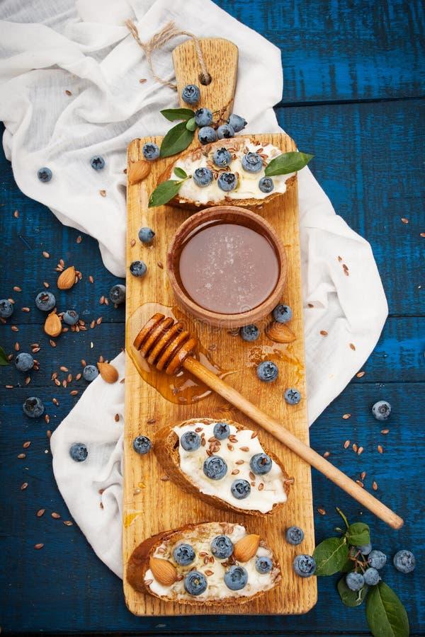 三明治用软干酪和蓝莓在木背景 健康的早餐 免版税库存照片