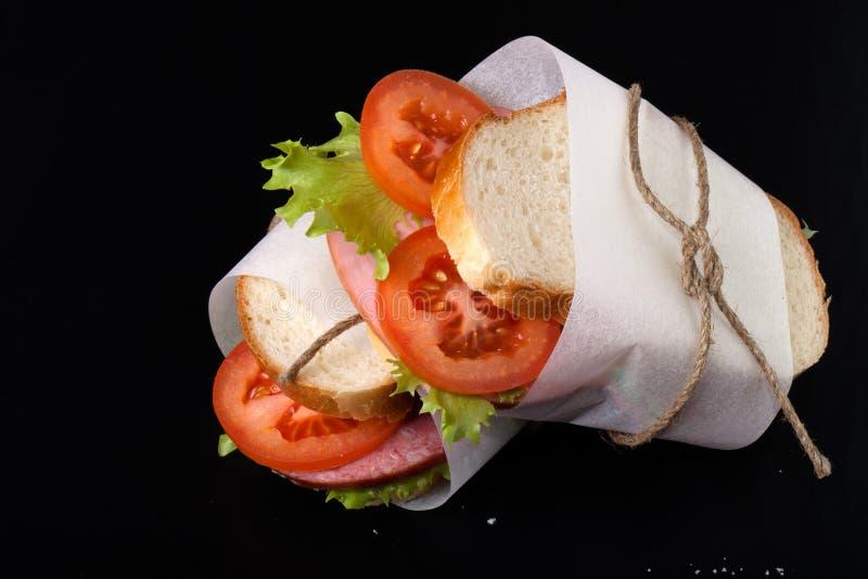 三明治用香肠包扎了在黑背景的麻线 与 免版税库存图片
