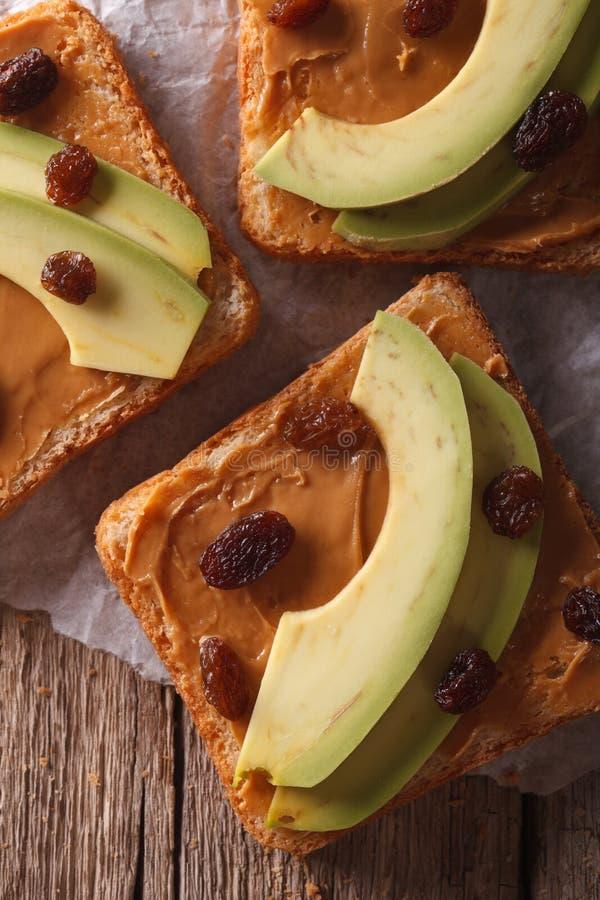 三明治用鲕梨、花生奶油和葡萄干宏指令 垂直 图库摄影