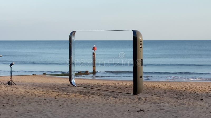 三星在海滩打电话 免版税库存图片