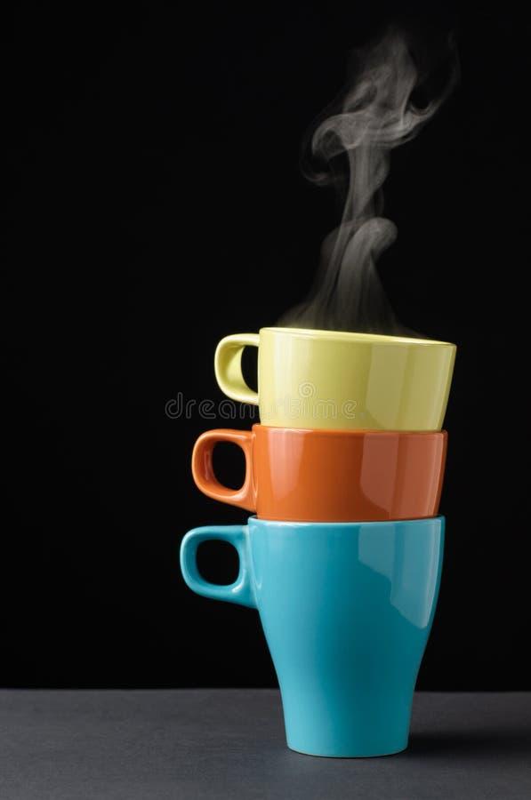 三有蒸汽的五颜六色的杯子 免版税库存照片