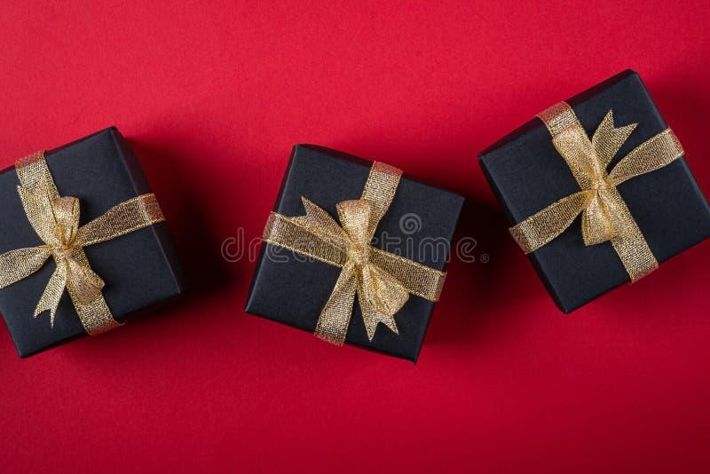 三有金黄丝带的黑礼物盒在红色纸背景,纹理,被隔绝的,顶视图的线 免版税库存图片