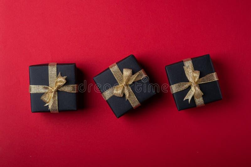 三有金黄丝带的黑礼物盒在红色纸背景,纹理,被隔绝的,顶视图的线 库存照片