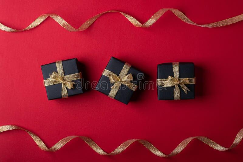三有金黄丝带的黑礼物盒在近线与在红色纸背景的扭转的丝带 库存图片