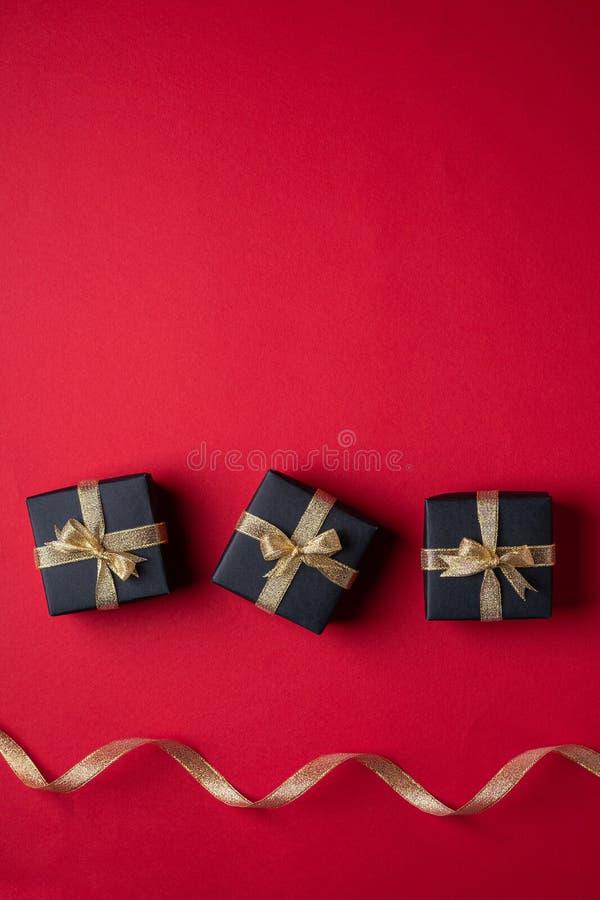 三有金黄丝带的黑礼物盒在近线与在红色纸背景的扭转的丝带 免版税库存照片