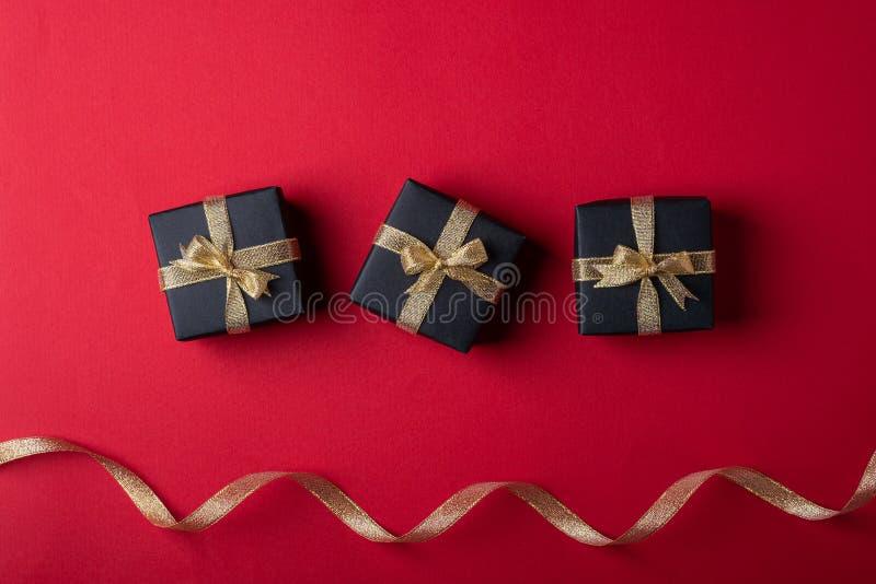 三有金黄丝带的黑礼物盒在近线与在红色纸背景的扭转的丝带 免版税图库摄影