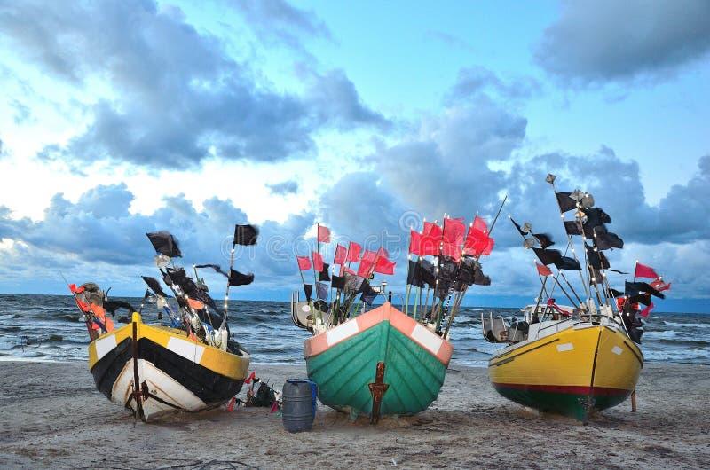 三条颜色小船在风暴前的沿海 免版税库存图片
