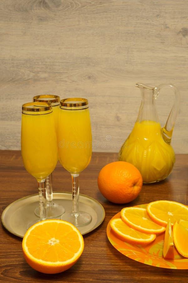 三杯含羞草鸡尾酒,有橙汁过去的,在一张木桌上的新鲜的桔子一个蒸馏瓶 免版税库存照片