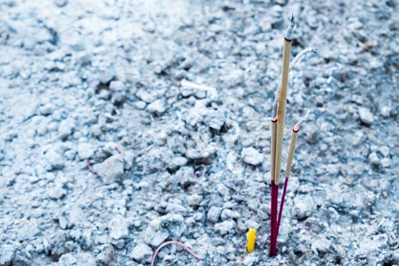 三根香火棍子和一个蜡烛在香火罐w烧 免版税库存图片