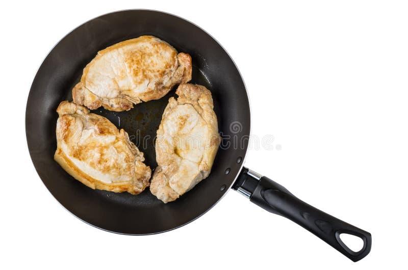 三油煎了在白色隔绝的煎锅的猪肉炸肉排 免版税库存照片