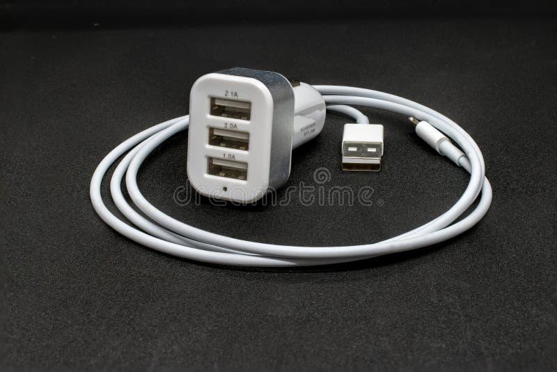 三港USB汽车香烟适配器和缆绳 库存图片