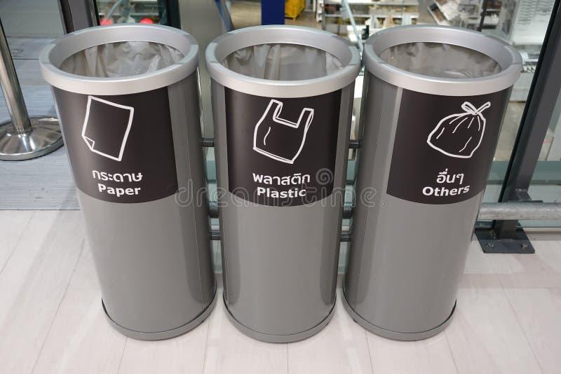 三灰色分开的塑胶容器,回收在纸、塑料和其他材料盖印的标志在前面 库存照片